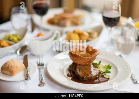 Rôti de bœuf accompagné de Yorkshire pudding aux légumes et sauce Banque D'Images