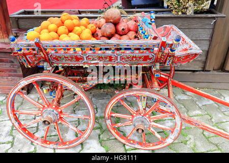 Abondamment fleuri rouge panier en bois peint contenant des oranges et des grenades sur la promenade de front de Banque D'Images