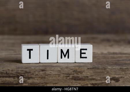 Le temps, écrit en cubes sur fond de bois Banque D'Images