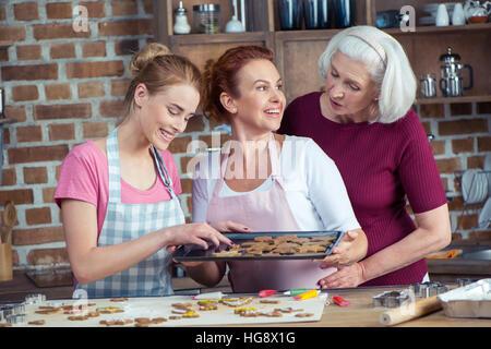 Une famille heureuse de trois générations ensemble making Christmas Cookies Banque D'Images