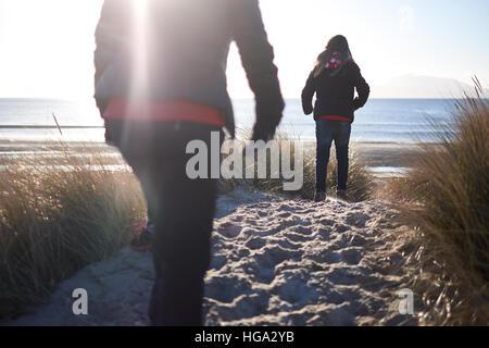Trois figures à pied le long d'un chemin à travers les dunes en direction de la plage sur une froide, claire, journée Banque D'Images