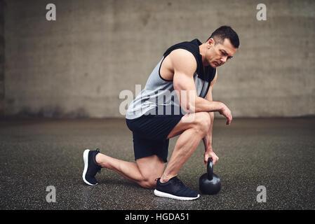 Flexion du genou de l homme musclé  Longueur totale du jeune homme tourné  en séance de sport et de flexion sur un genou c4c3e604b55