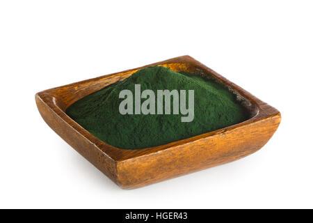 La spiruline en poudre dans un bol en bois isolé sur fond blanc. Superfood