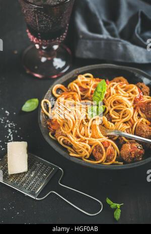 Spaghetti avec meatballas, feuilles de basilic, le parmesan et le vin rouge Banque D'Images