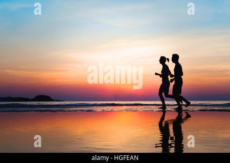 Le jogging et les modes de vie, deux silhouettes sur la plage au coucher du soleil, d'entraînement et le sport Banque D'Images