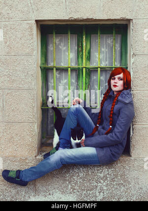 Jeune femme rousse, avec deux longues tresses, assis près d'une vieille fenêtre Banque D'Images