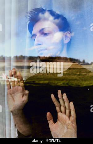 Jeune homme de rêver à la liberté à travers une fenêtre Banque D'Images