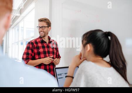 Happy young woman in casuals donnant présentation sur tableau blanc à ses collègues dans la salle de conférence. Banque D'Images