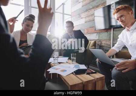 Groupe de jeunes gens d'affaires à une réunion au bureau. La discussion de nouvelles idées commerciales. Banque D'Images
