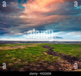 Paysage islandais typique avec des montagnes à l'horizon brumeux. Lever du soleil d'été colorés près du lac Myvatn, Banque D'Images