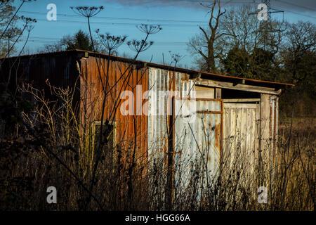 Hangar en tôles ondulées d'étain hut in field Banque D'Images
