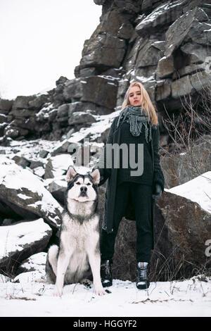 Fille avec chien malamute parmi les roches en hiver. Elle est debout au milieu des rochers et de la neige. Chien Banque D'Images