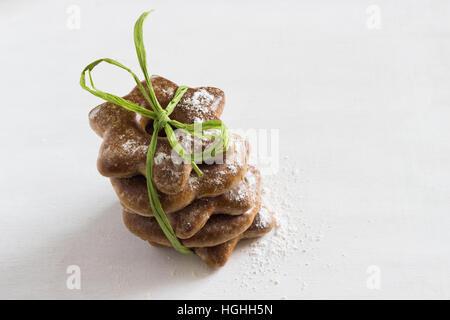 Décorées d'épices bavarois attaché avec string vert comme un cadeau et avec du sucre glacé en poudre sur le fond Banque D'Images