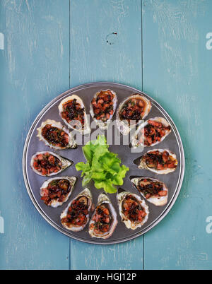 Huîtres au four kilpatrick sur spécial cuisson et desservant le plateau métallique Banque D'Images