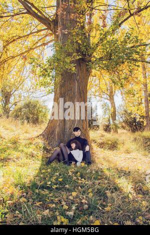 Jeune couple dans un parc en automne, s'appuyant sur un arbre Banque D'Images
