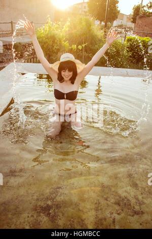 Jeune femme portant un bikini noir jouant avec de l'eau dans une piscine naturelle à l'été