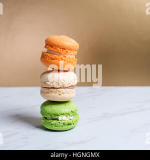 Macarons colorés et doux empilés sur une texture de marbre table et fond doré. Dessert traditionnel français. Copier Banque D'Images