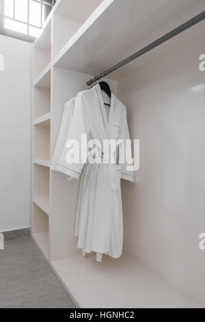 Robes blanches avec cintres en bois à dressroom. Banque D'Images