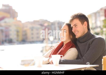 Couple assis sur une terrasse de l'hôtel de vacances avec un port à l'arrière-plan dans une journée ensoleillée Banque D'Images