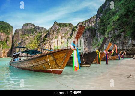 La Thaïlande vue mer plage rond avec des collines calcaires avec de nombreux bateaux longtail traditionnels de stationnement Banque D'Images