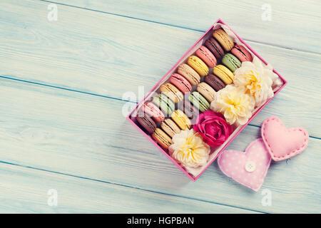 Macarons colorés sur la table en bois. Macarons sucrés en boîte-cadeau et des coeurs. Vue de dessus avec l'exemplaire Banque D'Images