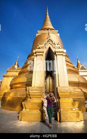 Touriste marche dans le Temple du Bouddha d'Émeraude près de grand stupa doré à Bangkok au coucher du soleil Banque D'Images
