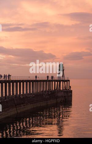 Au coucher du soleil, les gens et pier sont découpé sur le spectaculaire, lumineux, Rouge ciel et mer - Whitby, Banque D'Images