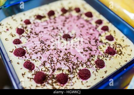 Cheesecake framboise en verre bleu pan décoré avec des copeaux de chocolat Banque D'Images