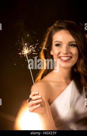 Belle brunette woman holding sparkler et célébrer Banque D'Images
