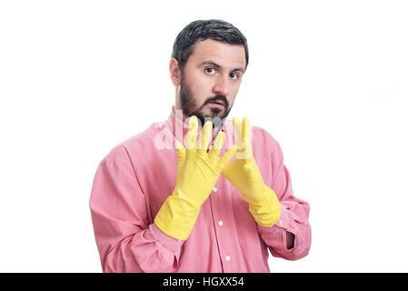 L'homme de nettoyage mettre gants en latex et se préparer à nettoyer la maison isolé sur fond blanc Banque D'Images