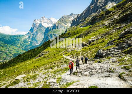 Randonneurs sur le sentier de la Suisse avec l'Eiger Grindelwald vallée ci-dessous et le Wetterhorn peak derrière Banque D'Images