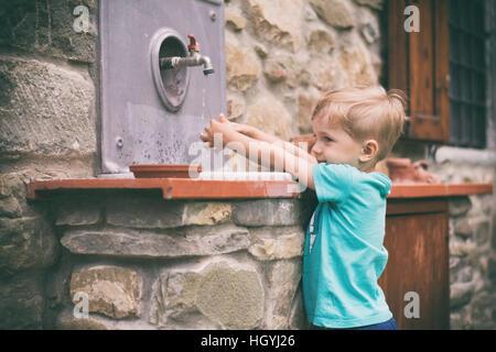 Petit garçon, se laver les mains sous le robinet dans le jardin Banque D'Images