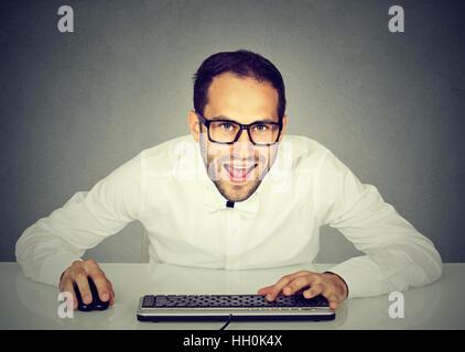 Les jeunes fous à la recherche d'affaires avec des lunettes de taper au clavier Banque D'Images