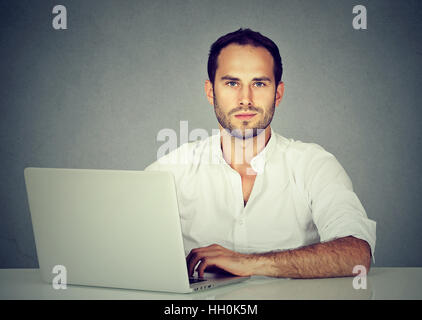 Smiling young man using a laptop Banque D'Images
