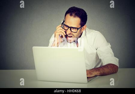 Jeune homme frustré et furieux en ligne et à crier sur un téléphone. L'expression des émotions négatives face Banque D'Images