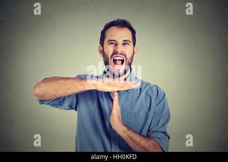 Man showing time out hand gesture, frustrés de crier d'arrêter isolé sur fond de mur. Trop de choses à faire débordé Banque D'Images