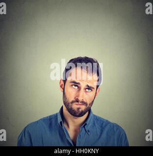 Gros plan portrait confus drôle homme sceptique jusqu'à la pensée isolé sur fond de mur gris avec copie espace au-dessus de la tête. Visage humain expressions,