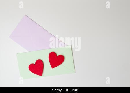 Deux enveloppes et l'impression coeurs rouges sur le tableau blanc. Vue d'en haut. Banque D'Images