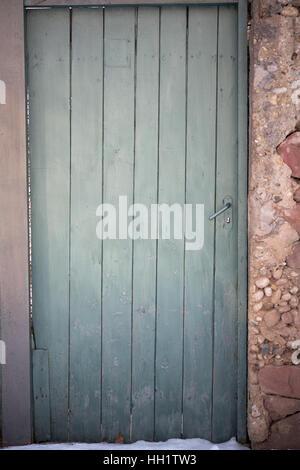 Vieille porte en bois vert dans le mur de pierre Banque D'Images