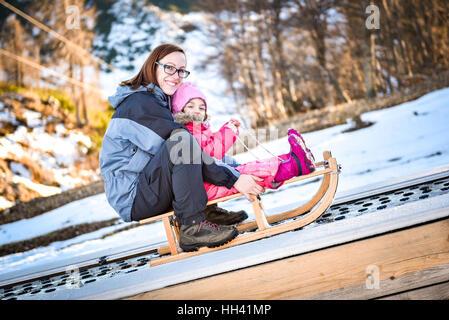 La mère et le petit enfant sur un convoyeur de ski sur un traîneau dans station de ski de l'école de ski. Banque D'Images