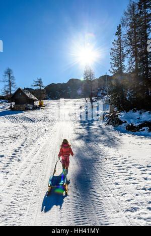 Fille tire-luges de ski de porter des vêtements d'hiver. Station de ski de haute montagne, vacances, maison de vacances Banque D'Images