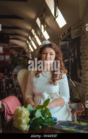 Le jeune est belle la jeune fille en robe blanche est assis sur une chaise à une grande fenêtre Banque D'Images