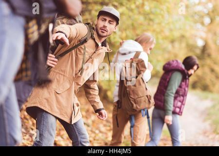 Quatre jeunes amis backpackers marcher dans la rangée en forêt d'automne Banque D'Images