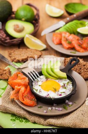 Œuf frit, d'avocat et saumon fumé dans une poêle pour le petit-déjeuner Banque D'Images