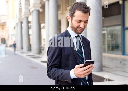 Businessman dans la ville en regardant son téléphone intelligent Banque D'Images