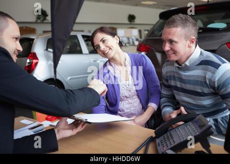 Couple de discuter avec un vendeur de voiture dans un magasin de voitures Banque D'Images