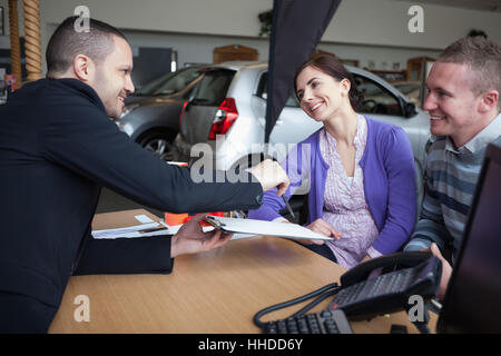 Vendeur de parler à un couple dans un magasin de voitures Banque D'Images