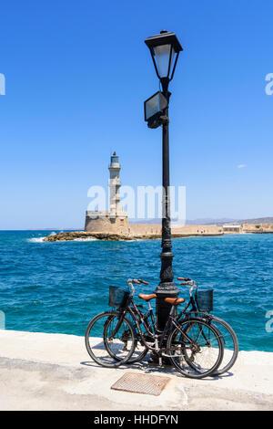 Des vélos sur la promenade du bord de mer en face de l'ancien phare dans le port vénitien de La Canée, Crète, Grèce Banque D'Images