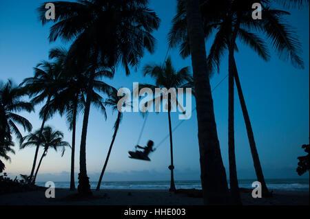 Une fille joue sur une balançoire à égalité entre les palmiers sur la côte des Caraïbes à Palomino en Colombie Banque D'Images