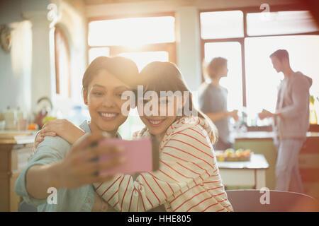Les jeunes femmes amis colocataires hugging en tenant avec selfies téléphone appareil photo Banque D'Images